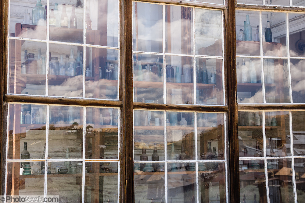 """Glass reflecting an abstract pattern of cumulus clouds obscures rows of bottles seen behind. These prominent windows front the finest home in Bodie, owned by James Stuart Cain from the 1890s - 1940s. Bodie is now California's official state gold rush ghost town. Jessie McGath originally built this house for his new wife in 1879, and JS Cain bought it in the 1890s. Cain moved to Bodie when he was 25 and built an empire starting with putting lumber barges on Mono Lake and transporting timber to support mine shafts, stoke boilers for machinery, build & heat buildings, and cook food. Cain eventually took control of the Stamp Mill though court action and went on to be the principal property owner and one of the richest men in town. Bodie State Historic Park lies in the Bodie Hills east of the Sierra Nevada mountain range in Mono County, near Bridgeport, California, USA. After W. S. Bodey's original gold discovery in 1859, profitable gold ore discoveries in 1876 and 1878 transformed """"Bodie"""" from an isolated mining camp to a Wild West boomtown. By 1879, Bodie had a population of 5000-7000 people with 2000 buildings. At its peak, 65 saloons lined Main Street, which was a mile long. Bodie declined rapidly 1912-1917 and the last mine closed in 1942. Bodie became a National Historic Landmark in 1961 and Bodie State Historic Park in 1962."""