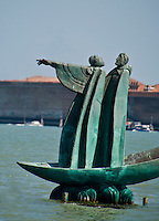 Bronze figures of a spirit in the lagoon pointing the way to Isola San Michel in Venice, Italy.