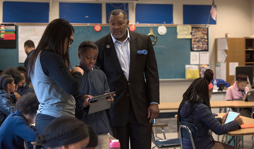 Superintendent Dr Anthony Hamlet observes math teacher Danielle Jackson (left) instructing seventh grader Adai Palmer on the iPad during a visit to Westinghouse High School.