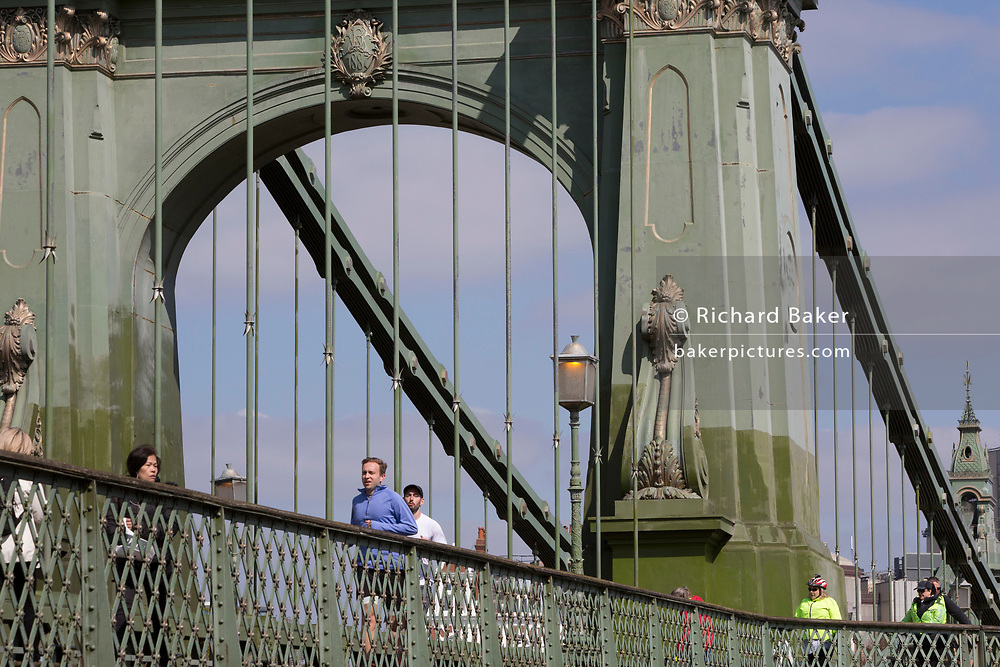 "After being closed indefinitely to all traffic due to structural faults, pedestrians walk across Hammersmith Bridge, on 11th April 2019, in west London, England. Safety checks revealed ""critical faults"" and Hammersmith and Fulham Council has said it's ben left with no choice but to shut the bridge until refurbishment costs could be met. The government has said that between 2015 and 2021 its is providing £11bn of support to the 132-year-old bridge."
