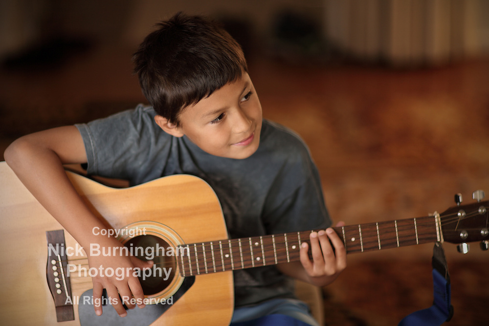 Young boy plays on a guitar