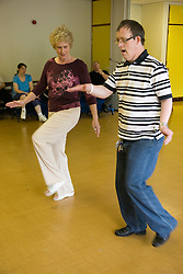Woman Day Service Officer teaching a day service users with learning disabilities a dance step,