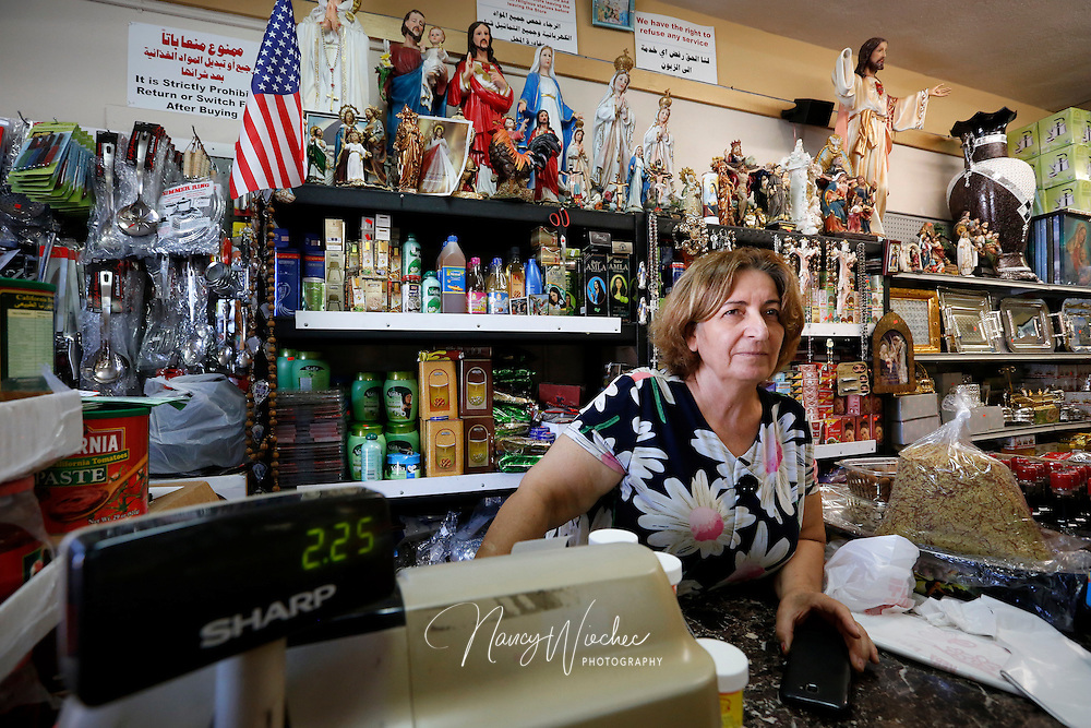 Chaldean Nancy Shimon tends the counter at her family's spice shop near Main Street in El Cajon, California, Aug. 14, 2015. Amid a variety of Middle Eastern spices, grocery goods and sundries, the store stocks religious statues, rosaries and crucifixes. (Nancy Wiechec for ONE magazine)
