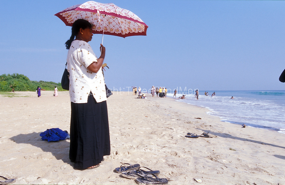 A local traveller stands on the beach protected from the sun with an umbrella. Nilaveli Beach on the East Coast. north of Trincomalee.