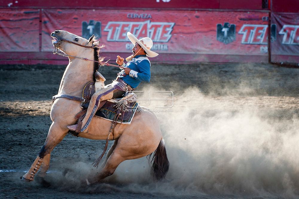October 1st, 2011. Pico Rivera, California. Traditional charros (Mexican cowboys) compete in a Mexican Rodeo. The competition at the Pico Rivera Sports Arena is a display of horsemanship and lasso skills. Pictured is Martin Alamillo. sliding his horse..PHOTO © JOHN CHAPPLE / www.johnchapple.com