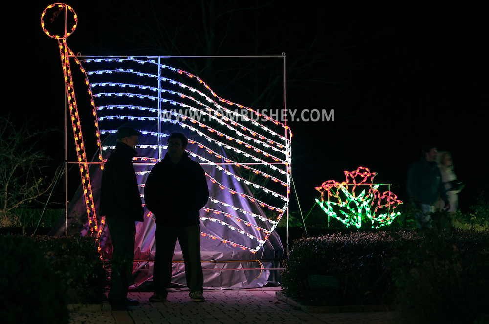 Hamptonburgh, New York - Two men stand in front of a large light display of the American Flag at the Holiday Lights in Bloom display at the Orange County Arboretum on Dec. 1, 2011. In observance of the tenth anniversary of Sept. 11, 2001,  Holiday Lights in Bloom expanded into the 9/11 Memorial Garden, which is decorated in patriotic colors.