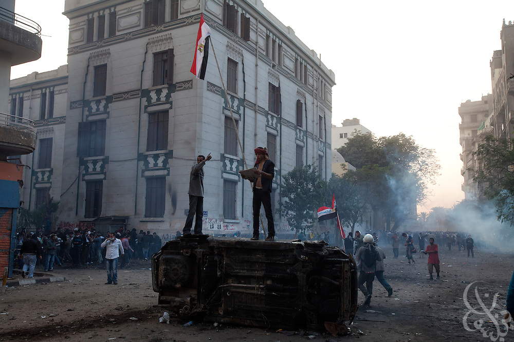 An Egyptian protestors calmly reads a newspaper atop a burned out car as tear gas canisters fired by nearby security forces land behind during street battles November 21, 2011 near Tahrir square  in central Cairo, Egypt. Thousands of protestors demanding the military cede power to a civilian government authority clashed with Egyptian security forces for a third straight day in Cairo, with hundreds injured and at least 24 protestors killed.  (Photo by Scott Nelson)