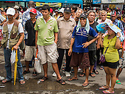 "07 AUGUST 2014 - BANGKOK, THAILAND:       People wait for a food distribution to start at Pek Leng Keng Mangkorn Khiew Shrine. Thousands of people lined up for food distribution at the Pek Leng Keng Mangkorn Khiew Shrine in the Khlong Toei section of Bangkok Thursday. Khlong Toei is one of the poorest sections of Bangkok. The seventh month of the Chinese Lunar calendar is called ""Ghost Month"" during which ghosts and spirits, including those of the deceased ancestors, come out from the lower realm. It is common for Chinese people to make merit during the month by burning ""hell money"" and presenting food to the ghosts. At Chinese temples in Thailand, it is also customary to give food to the poorer people in the community.    PHOTO BY JACK KURTZ"