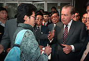 Former US President Richard M. Nixon speaks with a student as a crowd gathers during a walk around the Wangfujing Street shopping district October 30, 1989 in Beijing, China. Nixon visited as a private guest of the Chinese government.