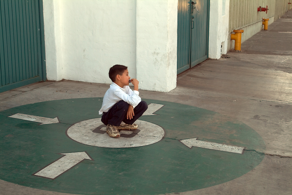 Young boy squatting on side street in Tecate, Mexico
