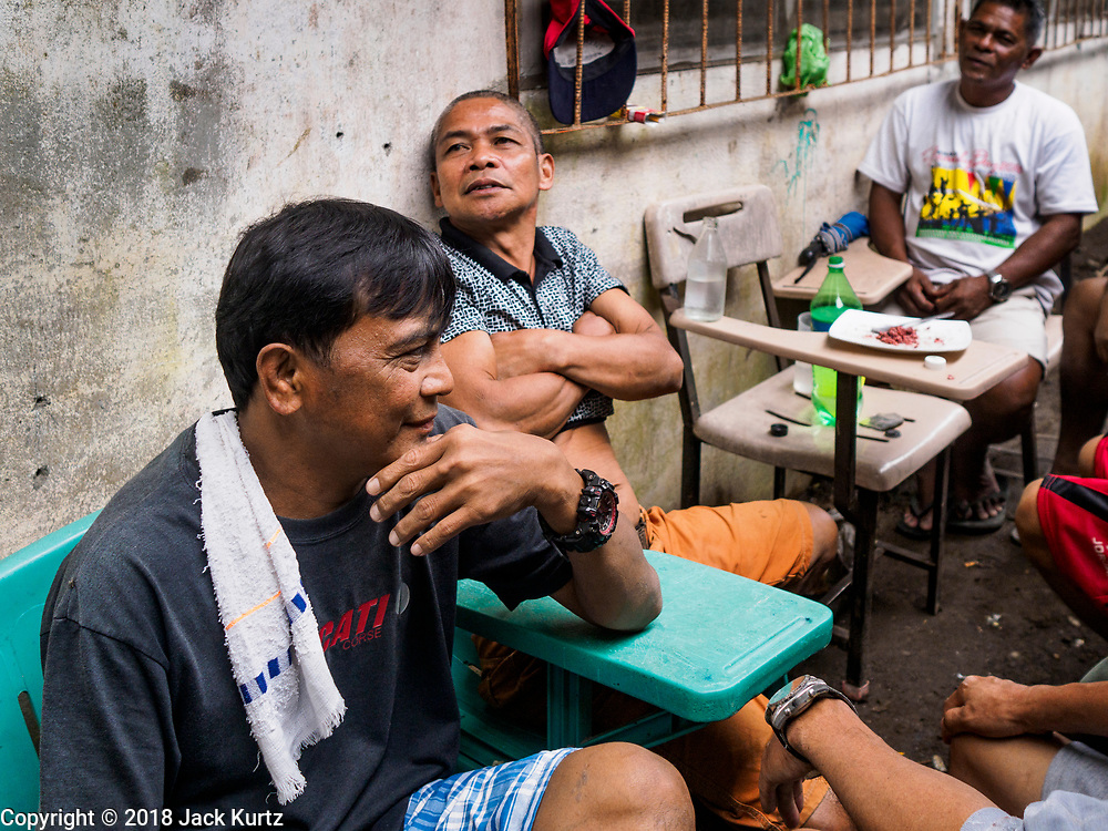 28 JANUARY 2018 - LEGAZPI, ALBAY, PHILIPPINES: Men relax on their only day off at the evacuation shelter for people from Barangay (community) Matanag in Albay Central School in Legazpi. They are construction workers and farmers and work a six day workweek. People from the community have been in the shelter since Mayon volcano started erupting two weeks ago. There are about 500 families at the shelter, around 2,000 people. More than 80,000 people have been evacuated from communities around the volcano and are living in shelters and camps outside of the evacuation zone. The Philippine government is preparing to house the people for up to three months.      PHOTO BY JACK KURTZ