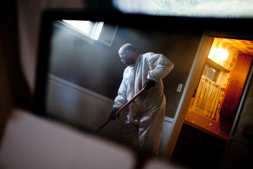 Timothy Tobola scrapes away the floor from a house in which a man had passed away. Saturday, March 17, 2012. La Crescenta, Calif. (photo by Gabriel Romero ©2012)