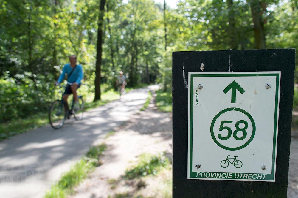 Een man fietst langs een bord van de knooppuntenroute bij de Soesterduinen.<br /> <br /> A cyclist is riding at the Soesterduinen.