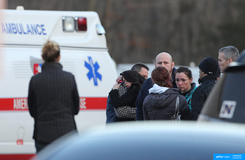 Unidentified people, believed to be parents and relatives, console each other at the fire station in Sandy Hook after today's shootings at Sandy Hook Elementary School, Newtown, Connecticut, USA. 14th December 2012. Photo Tim Clayton
