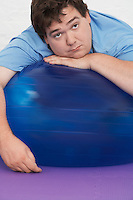 Overweight Man Resting on Exercise Ball portrait