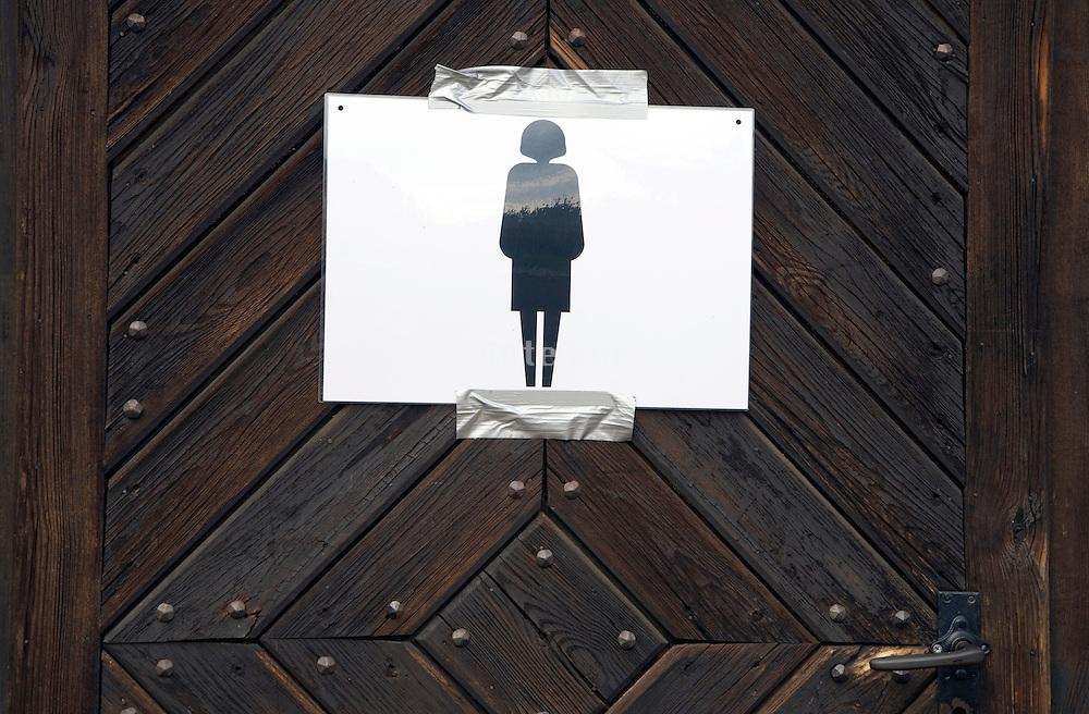 improvised temporary female toilet door sign on an old wooden door