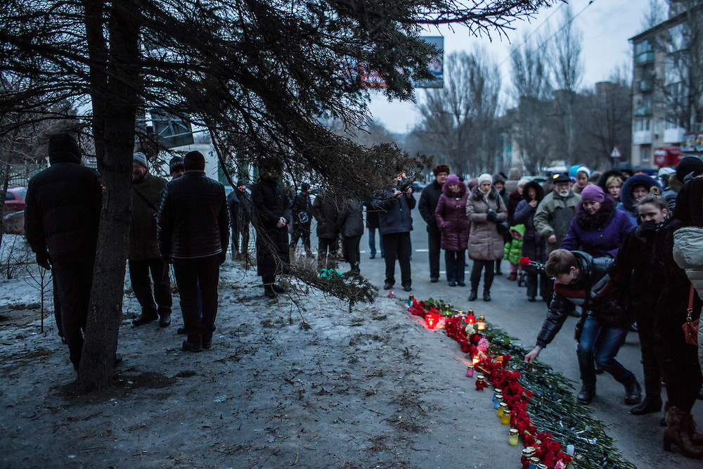 DONETSK, UKRAINE - JANUARY 24, 2015:  People lay flowers at a memorial event for victims of a rocket strike that hit a trolleybus two days earlier in Donetsk, Ukraine. The attack killed at least eight civilians and injured many more. CREDIT: Brendan Hoffman for The New York Times