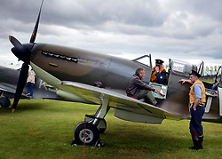© Licensed to London News Pictures. 16/09/2012. Goodwood, UK . Spitfire pilots take a break from display flying on the wings of their aircraft. People enjoy the atmosphere at the 2012 Goodwood Revival. The event recreates the glorious days of motor racing and participants are encouraged to dress in period dress. Photo credit : Stephen Simpson/LNP