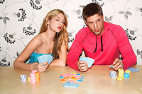 Young Couple sitting on sofa playing cards woman looking at cards of man