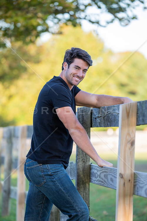 handsome All American man leaning against a rustic fence smiling