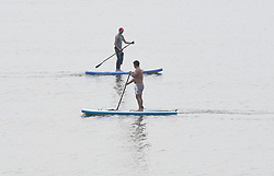 © Licensed to London News Pictures. 12/04/2020. Brighton, UK. Paddle boarders at Brighton beach at Brighton and Hove, during a pandemic outbreak of the Coronavirus COVID-19 disease.  Photo credit: Liz Pearce/LNP