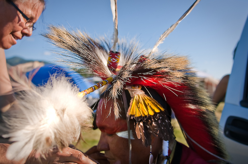 Debbie Buffalo, left, helps Ronald Crane tightly affix his hair roach, made from porcupine guard hair and whitetail deer fur and worn by the majority of male dancers, to the crown of his head through a lock of his hair.