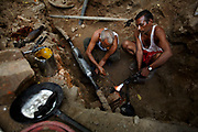 New Dehli, Dehli, IND, August 29th 2007: Ramjeelal (left) and his colleague are working hard to repair a broken electricity line that was cut by workers repairing another cable. Ramjeelal is sealing the makeshift repair with lead, hoping to make it water proof.<br /> The demand for comfort and luxury clashes with failing infrastructure in New Dehli.