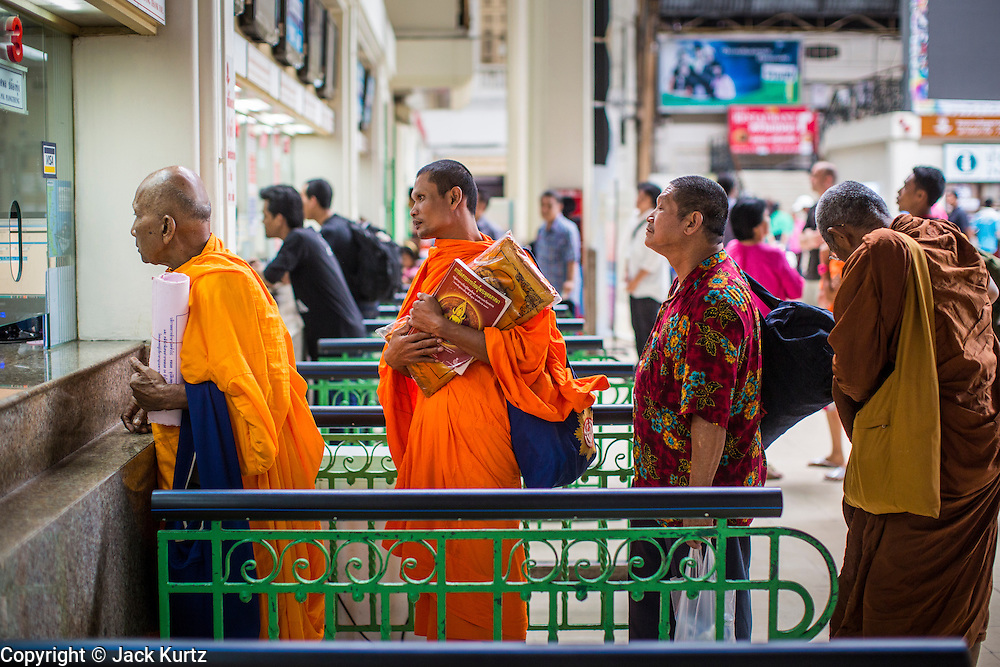 17 APRIL 2013 - BANGKOK, THAILAND:   Buddhist monks buy train tickets in Hua Lamphong Train Station after Songkran. Songkran, the traditional Thai New Year, is the busiest time of the year for Thai domestic travel. Many people in Bangkok return to their home provinces for the holiday and some people in the provinces travel to Bangkok for the holiday. Songkran, usually a three day holiday, was five days this year because the official days on the weekend. Trains and buses coming into Bangkok were reported to be fully booked and the State Railway of Thailand added extra trains and carriages to accommodate the crowds.  PHOTO BY JACK KURTZ