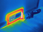 Thermogram of shoes next to a heat duct.  The different colors represent different temperatures on the object. The lightest colors are the hottest temperatures, while the darker colors represent a cooler temperature.  Thermography uses special cameras that can detect light in the far-infrared range of the electromagnetic spectrum (900?14,000 nanometers or 0.9?14 µm) and creates an  image of the objects temperature..