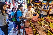 12 AUGUST 2013 - MACAU: A vendor cuts up pork bakkwa in a bakery in Macau. Bakkwa, also known as rougan, is a Chinese salty-sweet dried meat product similar to jerky. Bakkwa is made with a meat preservation and preparation technique originating from China.  Macau, also spelled Macao, is one of the two special administrative regions of the People's Republic of China (PRC), the other being Hong Kong. Macau lies on the western side of the Pearl River Delta across from Hong Kong to the east, bordered by Guangdong province to the north and facing the South China Sea to the east and south. The territory's economy is heavily dependent on gambling and tourism, but also includes manufacturing.     PHOTO BY JACK KURTZ