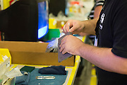 An employee cleans a Nintendo NES game at the GameStop retro classics console games refurbishment center in Grapevine, Texas on June 24, 2015. (Cooper Neill for Mashable)