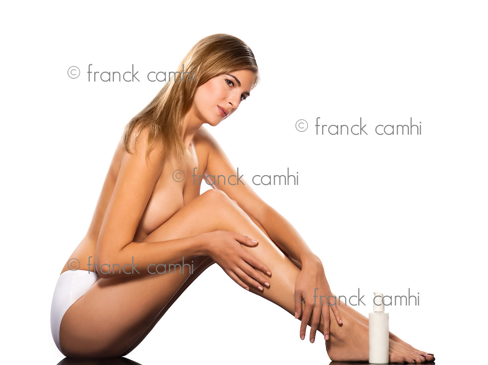 Portrait of a beautiful topless woman applying moisturizer on leg isolated on white background