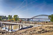 Nederland, Nijmegen, 20-4-2017 Een kleine nevengeul van de Waal bij Nijmegen is bijna klaar. Grootste onderdeel van de vele werken van Rijkswaterstaat om bij hoogwater een betere waterafvoer in de rivier te hebben. Een voetgangersbrug, voor wandelaars naar het recreatiegebied Waalstrand in de Ooijpolder. Ruimte voor de rivier, water, waal.  The Netherlands, Nijmegen Measures taken by Nijmegen to give the river Waal, Rhine, more space to flow during highwater and to prevent the risk of flooding. Room for the river. Reducing the level, waterlevel. Project to create two new paralel gullies, an extra flow of water, so the river can drain more water during highwater. Due to climate change and expected rise, increase of the sealevel, the Dutch continue to protect their land from the water. Foto: Flip Franssen