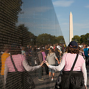 The Vietnam Veterans Memorial in Washington, D.C. honors members of the U.S. armed forces who fought in the Vietnam War, and those who died during service in Vietnam/South East Asia, and the Missing In Action from the War. Visitors touch, caress and rub names on the onto papers. The Washington Memorial can be seen in the background. The memorial was designed by American architect Maya Lin<br /> Photography by Jose More