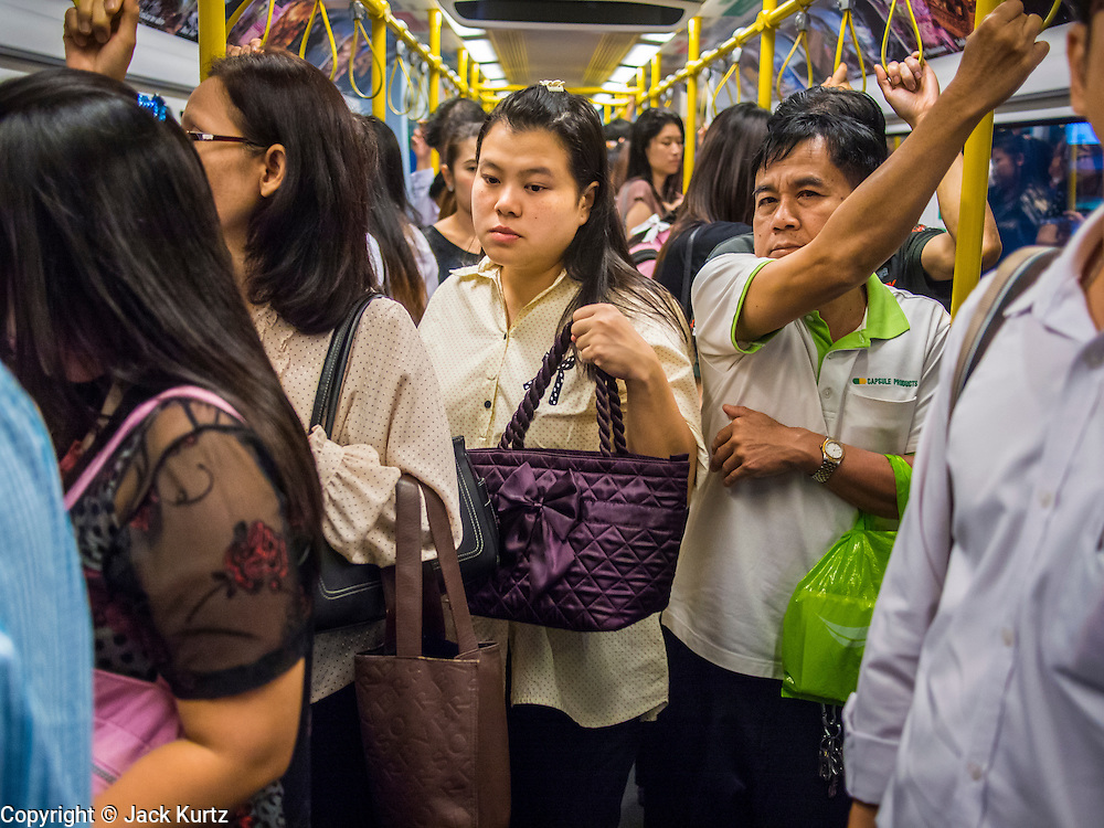 """22 AUGUST 2013 - BANGKOK, THAILAND:    Commuters on the Airport Rail Link, a train that connects Bangkok to Suvarnabhumi International Airport ride to work in Bangkok. Thailand entered a """"technical"""" recession this month after the economy shrank by 0.3% in the second quarter of the year. The 0.3% contraction in gross domestic product between April and June followed a previous fall of 1.7% during the first quarter of 2013. The contraction is being blamed on a drop in demand for exports, a drop in domestic demand and a loss of consumer confidence. At the same time, the value of the Thai Baht against the US Dollar has dropped significantly, from a high of about 28Baht to $1 in April to 32THB to 1USD in August.    PHOTO BY JACK KURTZ"""