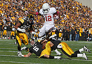 October 22, 2011: Indiana Hoosiers running back Stephen Houston (12) jumps over Iowa Hawkeyes defensive back Tanner Miller (5) and Iowa Hawkeyes defensive back Jordan Bernstine (4) during the first half of the NCAA football game between the Indiana Hoosiers and the Iowa Hawkeyes at Kinnick Stadium in Iowa City, Iowa on Saturday, October 22, 2011. Iowa defeated Indiana 45-24.