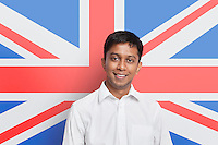 Portrait of young Asian man in shirt smiling against British flag