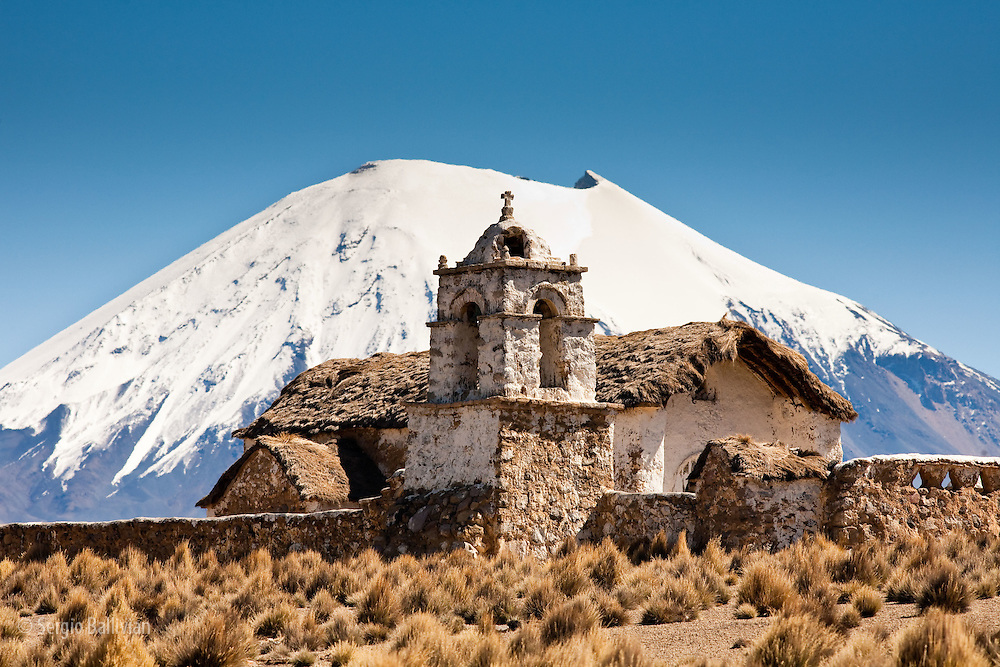 An old colonial-era church located on the high-altitude Altiplano in Sajama National Park in Bolivia is dwarfed by the Chungara Volcano that lies just over the border in neighboring Chile.