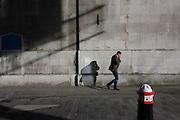 City of London bollard and businessman's shadows on church wall.