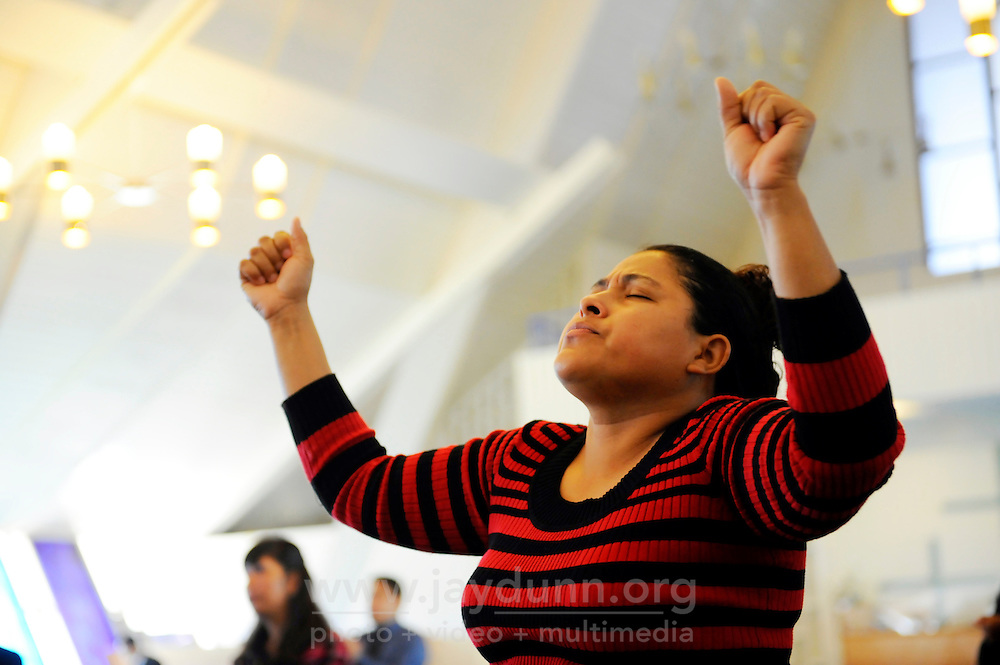 In an airy, open sanctuary lit by street-level stained glass, a parishioner raises her hands high during an early morning Easter Sunday service at Cristo La Roca Church in East Salinas.