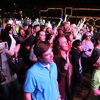 "Amory Railroad Festival attendees sing along to a cover of ""Faithfully"" by Resurrection: A Journey Tribute during opening night of the festival."