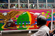 A colorful bus filled with tourists is driving on a city street that links the towns of Tachilek, Burma (Myanmar) and  Mae Sai, (Sae) Thailand.  The area is converged upon by throngs of Thai visitors and foreign tourists that cross the adjacent international border each year.