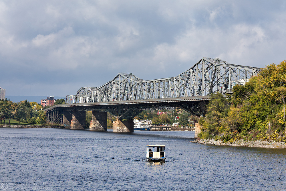 The Alexandra Bridge crosses the Ottawa River between Gatineau, Québec and Ottawa, Ontario.  The Aqua Taxi shuttles visitors between the Rideau Canal Dock and the Museum Dock across the Ottawa River in Gatineau, Québec.  Photographed where the Rideau Canal Locks meet the Ottawa River in Ottawa.