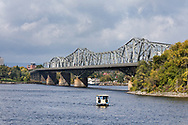 The Alexandra Bridge crosses the Ottawa River between Gatineau, Québec and Ottawa, Ontario.  The Aqua Taxi shuttles visitors between the Rideau Canal Dock and the Museum Dock across the Ottawa River in Gatineau, Québec.  Photographed where the Rideau Canal Locks meet the Ottawa River in Ottawa.