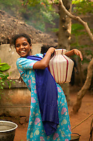 young girl carrying water from a well