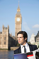 Thoughtful young businessman with book against Big Ben clock tower, London, UK