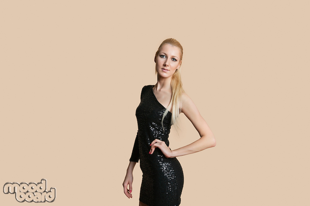 Portrait of a beautiful blond woman wearing cocktail dress with hands on hips over colored background