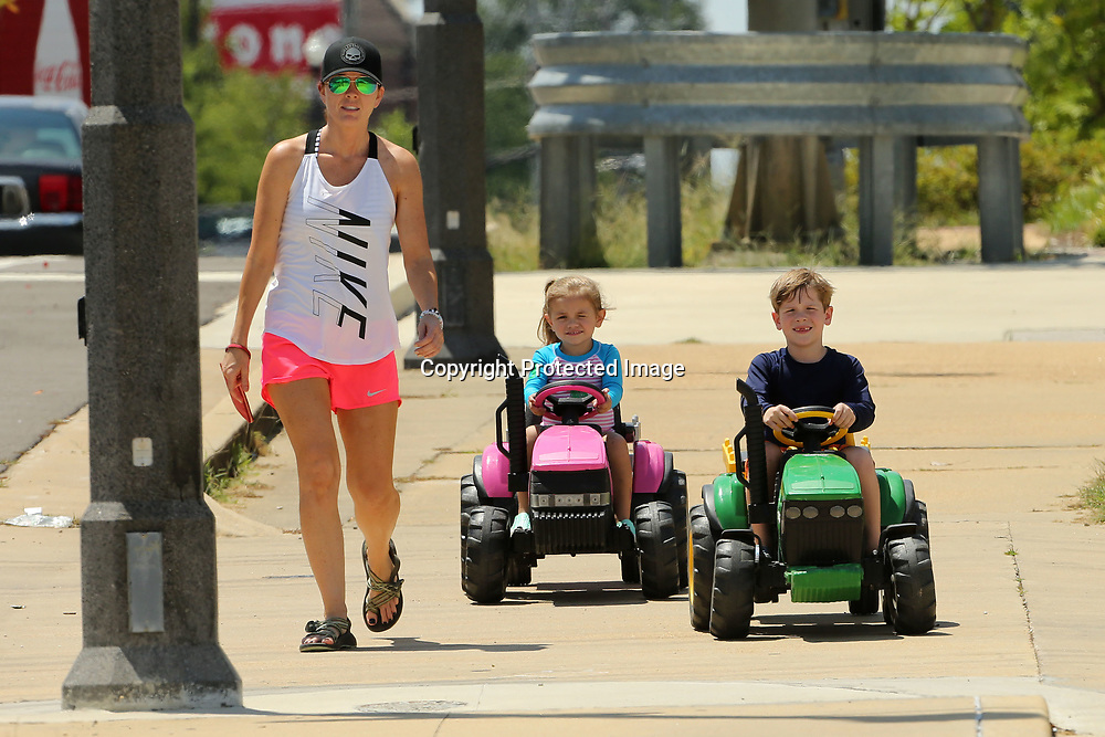 Leslie Hall, of Tupelo, walks with her children, Londyn, 3, and Cannon, 6, as they drive their tractor Power Wheels down Main Street on their way to play at Fairpark in downtown Tupelo Tuesday afternoon.