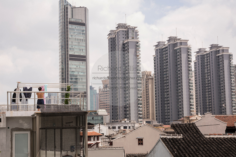 A man hangs laundry against the modern skyline of Shanghai, China