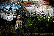 Bride sitting down on grassy patch and graffity wall on background. West bottoms, Kansas City wedding photography